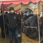 Ganymede Truffles Lachie looking cold standing next to a banner reading Canberra Truffle Festival Taste the Magic here