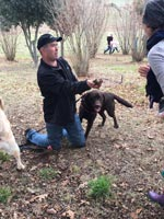 man holding truffle in the woods with a dog