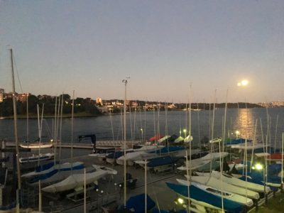 Full moon over Sydney Harbour with sail boats and masts in the twilight
